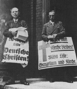 """Christentum und AfD, wer ist hier der """"echte"""" Christ? Das Bild zeigt einen Anhänger der """"Deutschen Christen"""" und einen Anhänger der Liste """"Evangelium und Kirche"""" mit umgehängten Wahlplakaten"""